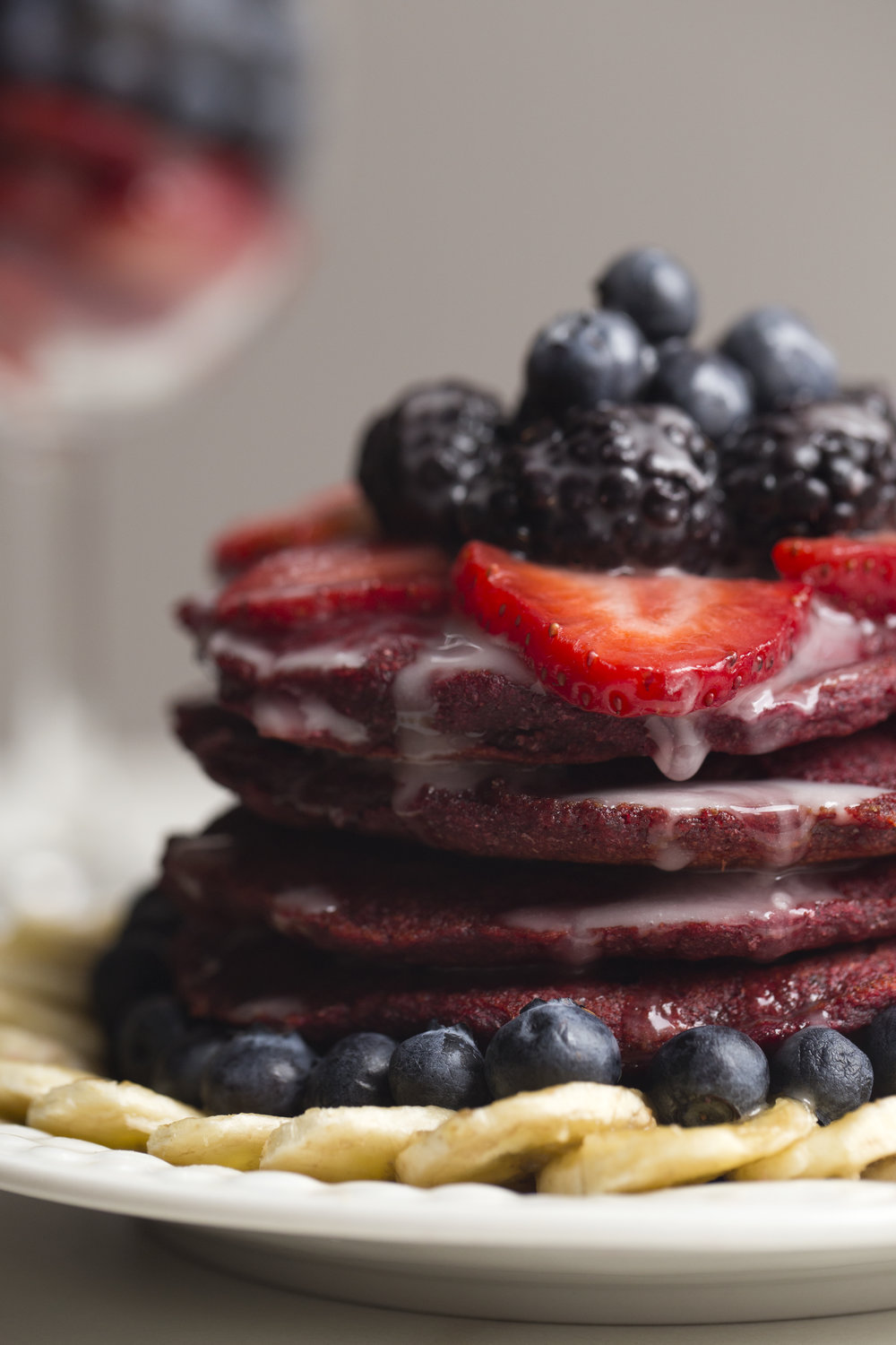 vegan red velvet pancakes covered in a bounty of fresh fruit and homemade icing.