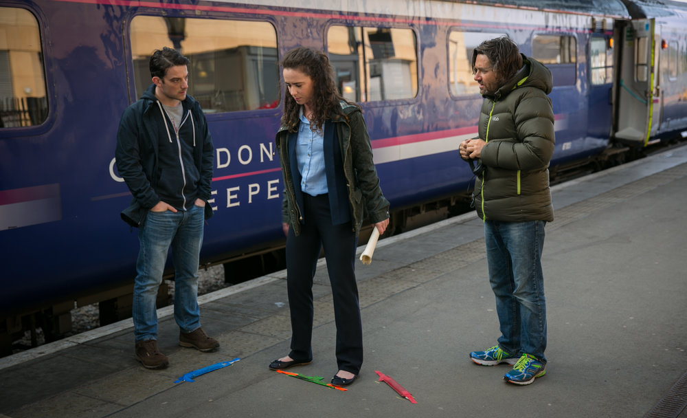 Director Simon Hunter with Amy Manson and Kevin Guthrie at Inverness station in Scotland.