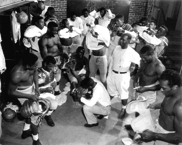 Coach_Jake_Gaither_(standing,_middle,_white_shirt)_in_the_locker_room_with_his_Florida_Agricultural_and_Mechanical_University_(FAMU)_football_team.jpg