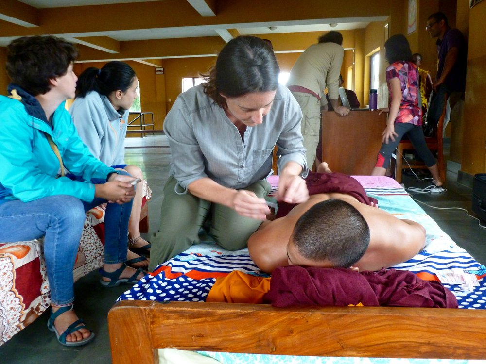 Treating shoulder pain in one of the monks.