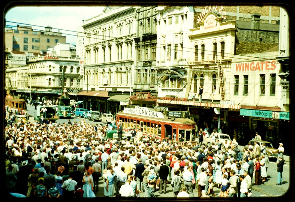 LAST TRAM: In December 1956 - Looking south along the west side of Lower Queen Street, showing a crowd gathered around Auckland's last tram in front of the Oxford movie cinema. (Sir George Grey Special Collections, Auckland Libraries, 1207-881)