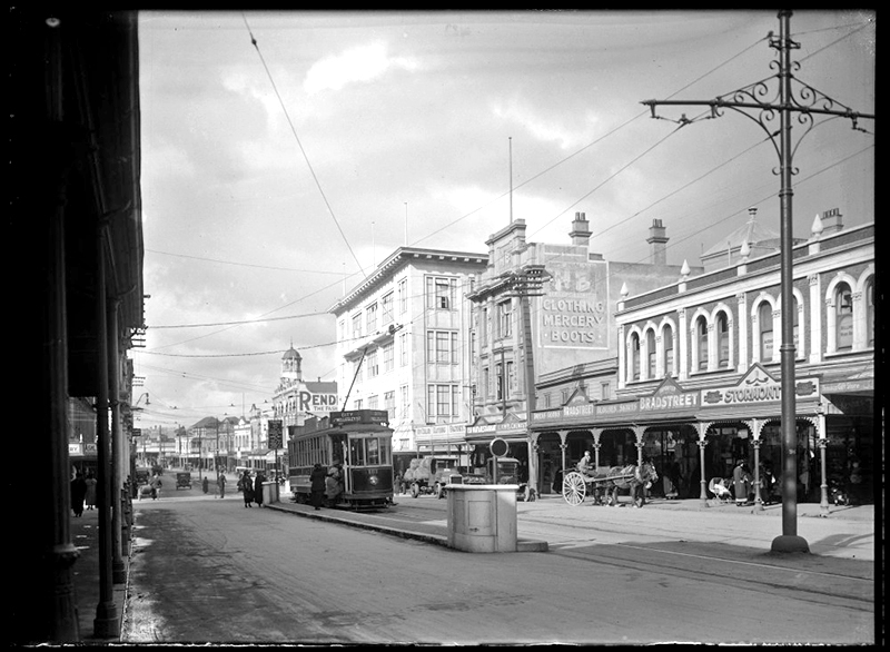 1920s K RD: Looking east from vicinity of bend opposite East Street down Karangahape Road, showing premises of Rendells Limited, George Court and Sons Limited, Hallenstein Brothers Limited, Sanford Limited, A S J Lamb, J A Bradstreet and J A Starmont and Sons. Also showing people hopping on tram headed for Wellesley Street (Photo: Sir George Grey Special Collections, Auckland Libraries, 1-W380)