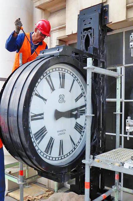 Worker removing old clock from outside the CPO building