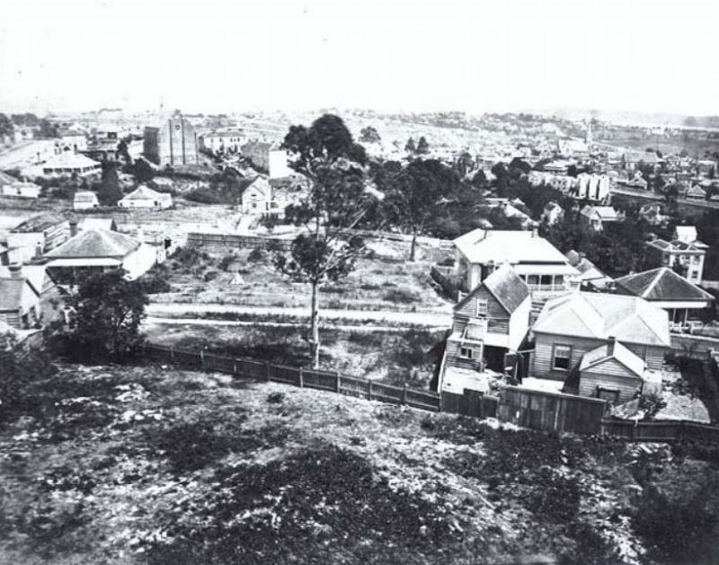 1870s: Looking west north west from Partington's Windmill, showing part of Karangahape Road (extreme left, distance), the Naval Hotel behind (left), Pitt Street Methodist Church (left distance), Liverpool Street (foreground), Queen Street, (centre obscured), Myers Park area (centre), St James Church and Greys Avenue (right distance)  Photo: Sir George Grey Special Collections, Auckland Libraries, 29-ALBUM-100-1