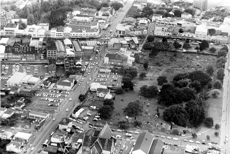 1964 VIEW: Looking north over part of Symonds Street Cemetery, now partly occupied by the Northern Motorway, showing Upper Queen Street, (vertically centre left), Queen Street (top centre), Karangahape Road, left to right (top), Alex Evans Street (formerly East Street), (bottom), with St Benedicts Church (foreground) (Photo: Sir George Grey Special Collections, Auckland Libraries, 580-10446)