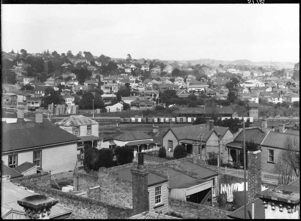 HOW IT WAS: How Mt Eden train station looked in 1931. This view is looking south from the roof of Trucks Limited in New North Road (formerly Eden Crescent) across Mount Eden, showing Flower Street, (left to right across foreground), railway lines and Mt Eden Railway Station (right of centre). (Photo: Sir George Grey Special Collections, Auckland Libraries, 4-5172)
