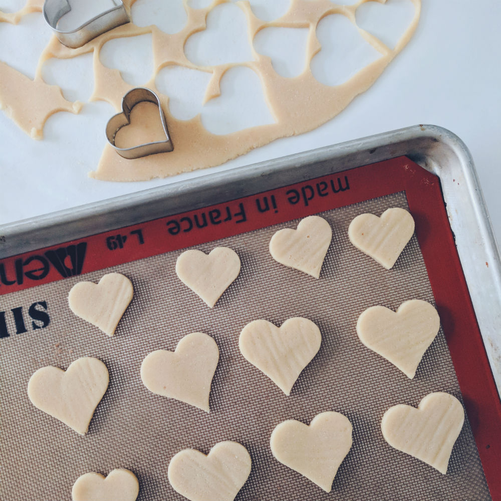 Almond sugar cookies stamped as hearts, ready for the oven.