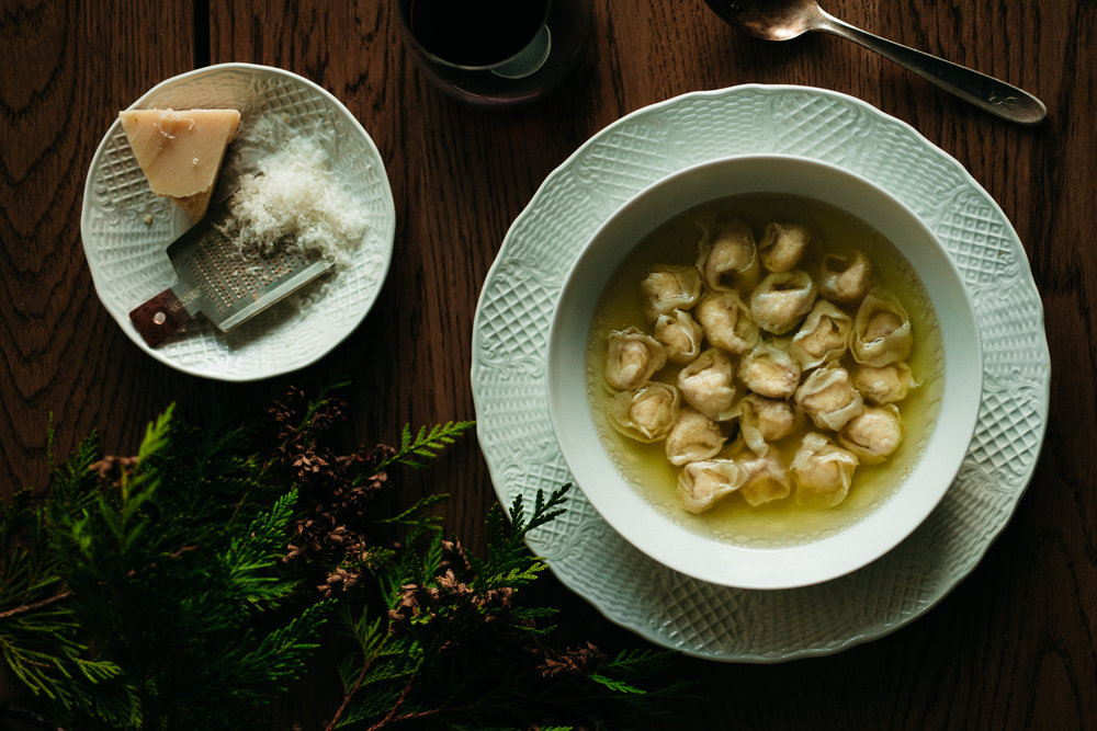 Tortellini in brodo, served with extra parmesan and Lambrusco wine. A Christmas dish from Emilia-Romagna.