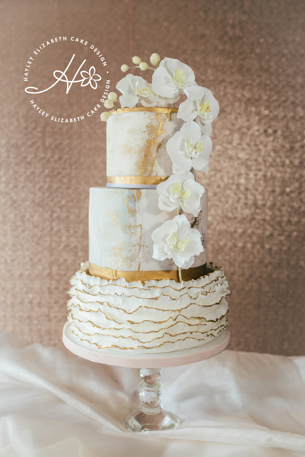 marble-andgold-splatter-wedding-cake-with-orchids.jpg