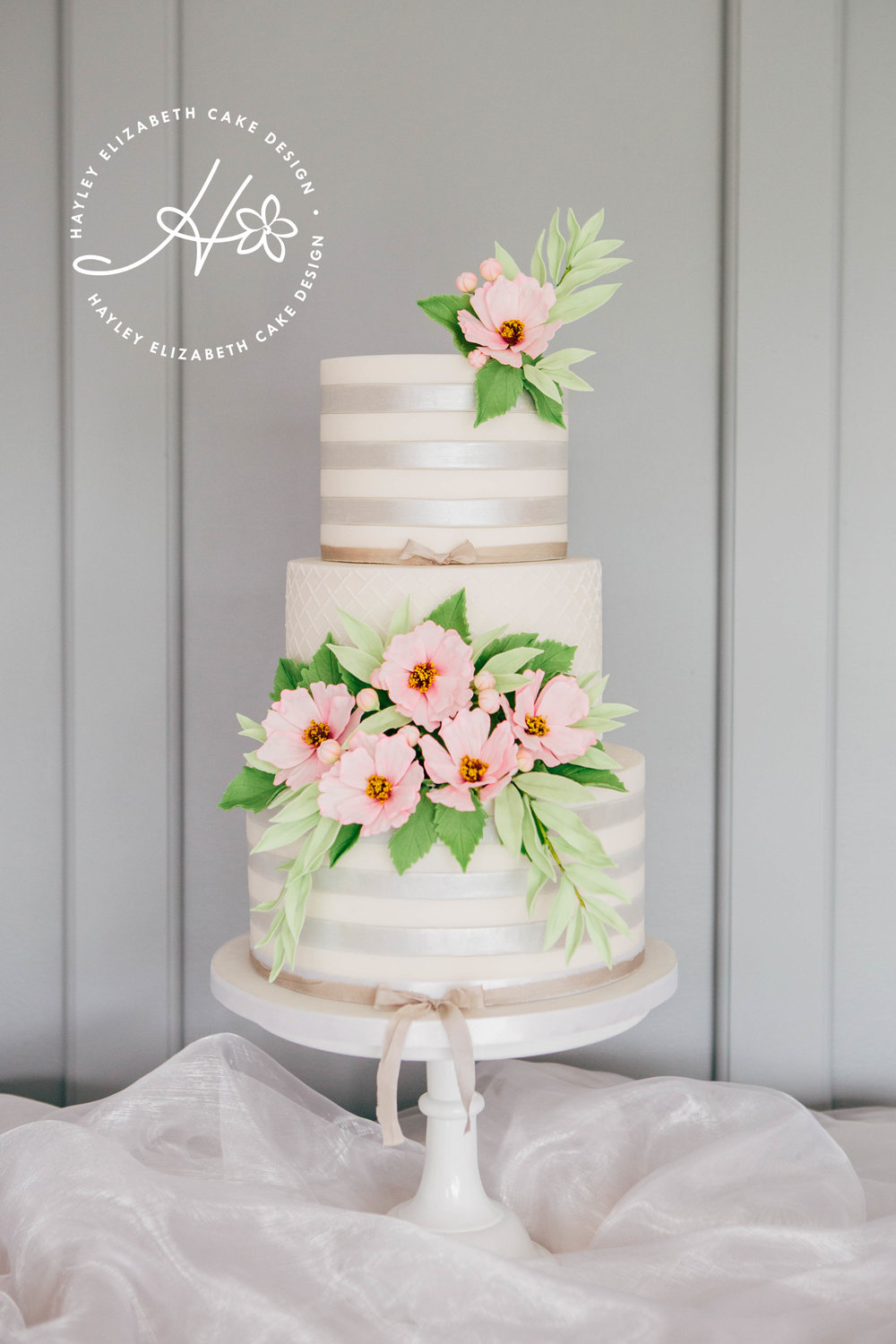 silver-shimmer-stripe-wedding-cake-with-pink-cosmos-and-foliage.jpg