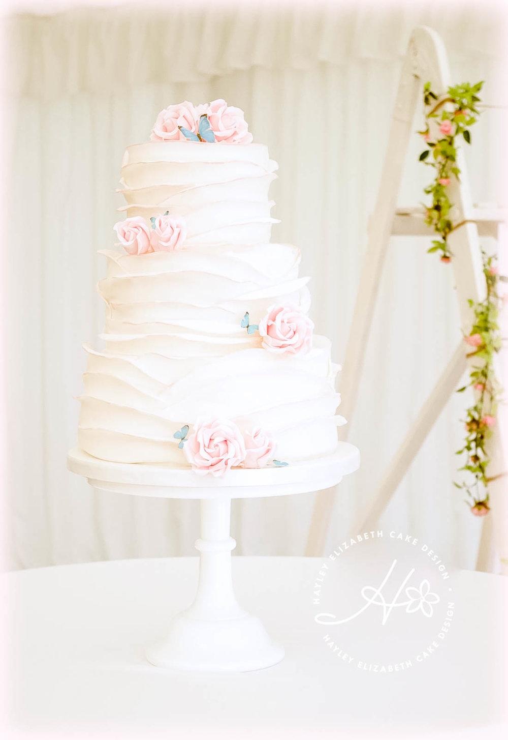 white-ruffle-wedding-cake-with-pink-painted-edge.jpg