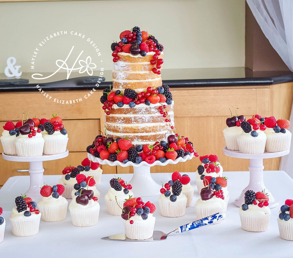 naked-wedding-cake-with-summer-berries-and-cupcakes.jpg