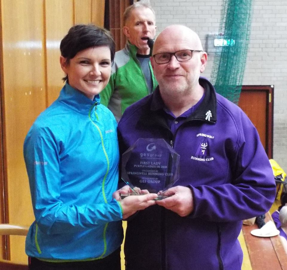 Race Director Kenny Bacon presents the GES Purple Ladies 5k trophy to Ciara Toner.