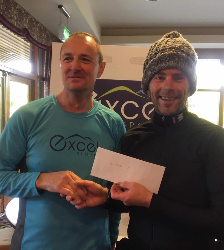 Eunan Quinn from Excel Sports presents Springwell RC's Colin Loughery with his Age Category win.