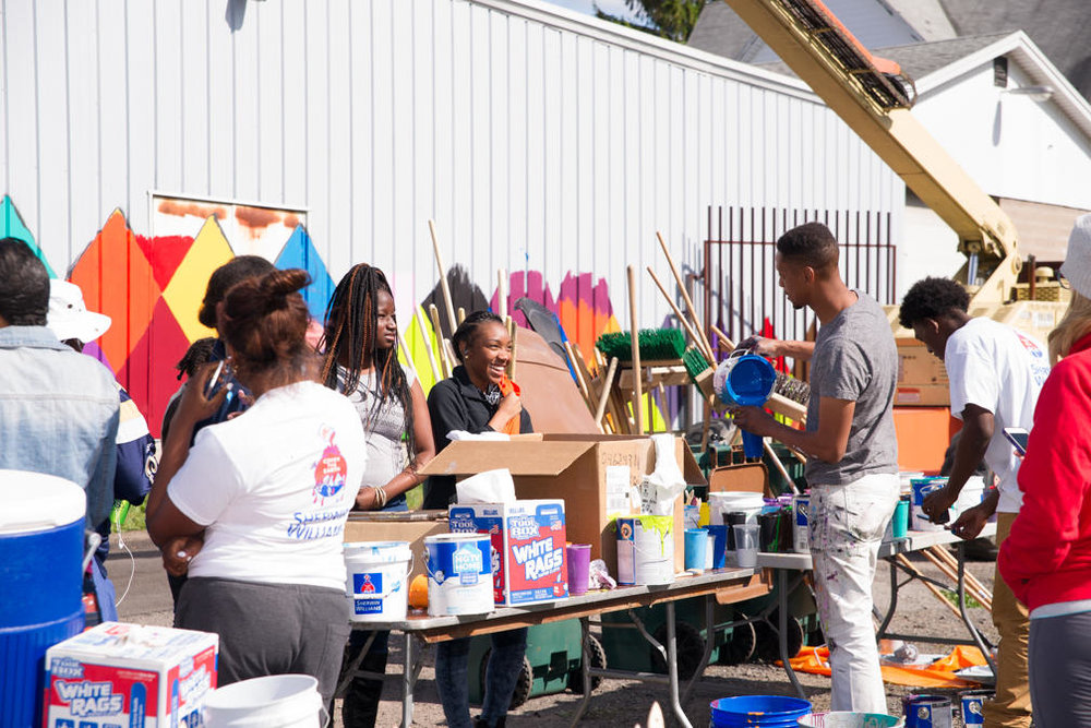 "Community ""Paint-out"" to paint murals in a city neighborhood."