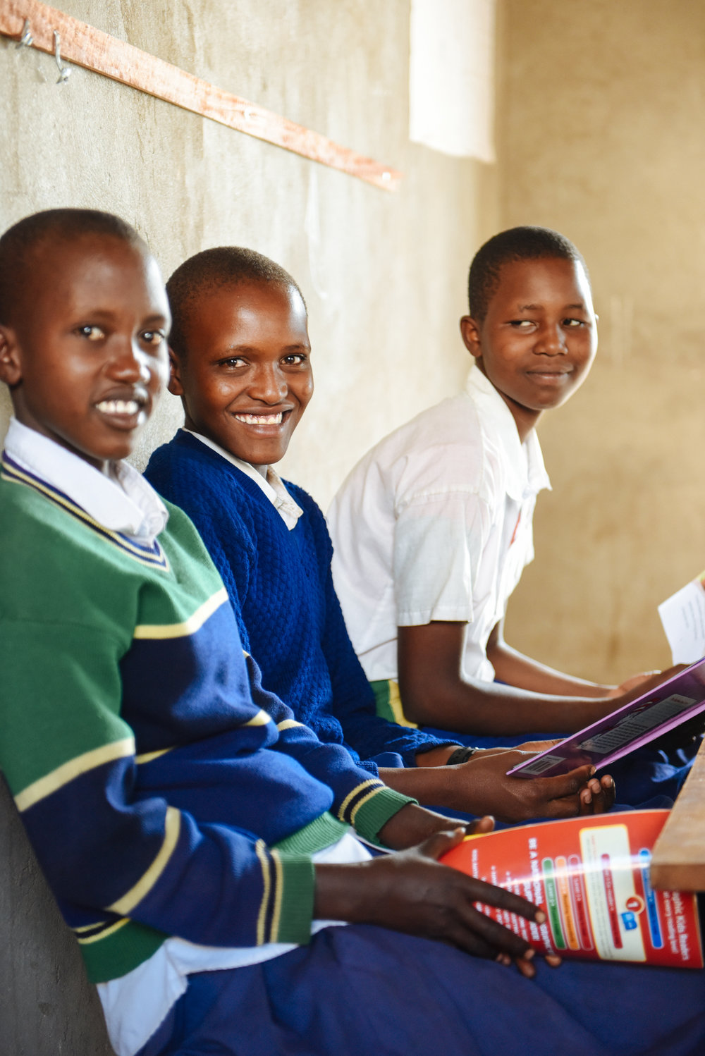 Martha, center, smiles during her Standard 7 class at Mlima Shabaha School.