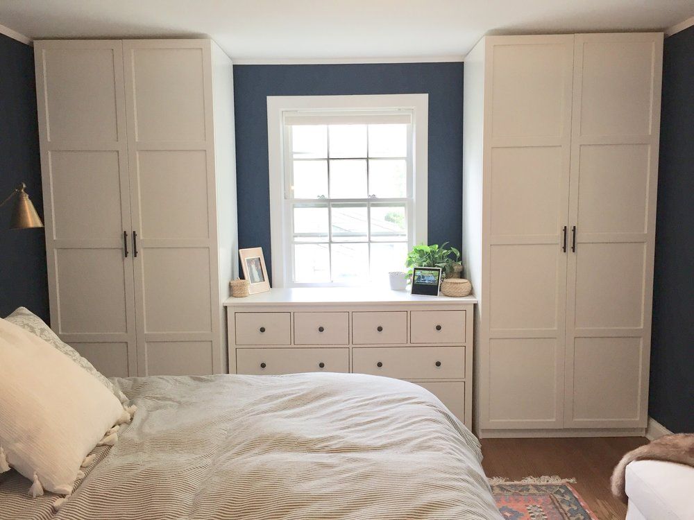 "Modern Urban farmhouse, Dark blue and white bedroom, ""Gentlemans Gray"" by Benjamin Moore. IKEA Pax system with Hemnes door, Hemnes dresser and grey french ticking duvet cover. Closet hardware oil rubbed bronze from Houzz. IKEA storage ottoman. Urban Outfitters floor pillow with tassels on bed. Faux fur throw from Wayfair. Rejuvenation rug. Design by Beam&Bloom."