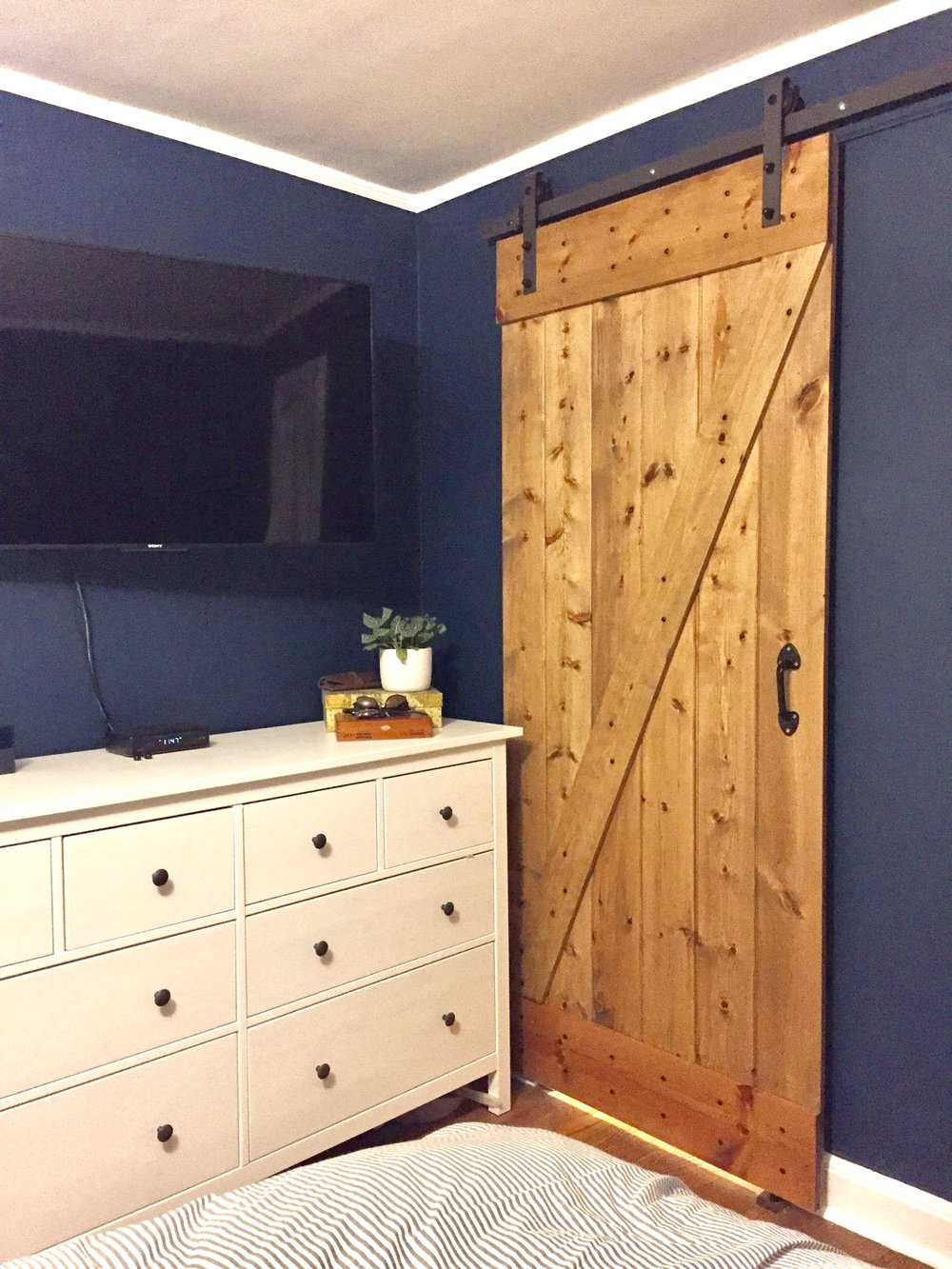 "Dark blue and white bedroom, ""Gentlemans Gray"" by Benjamin Moore. White Hemnes dresser from IKEA, rustic farmhouse Barn Door kit from Overstock and floor with 50/50 weathered oak and special walnut stain. Design by Beam&Bloom."