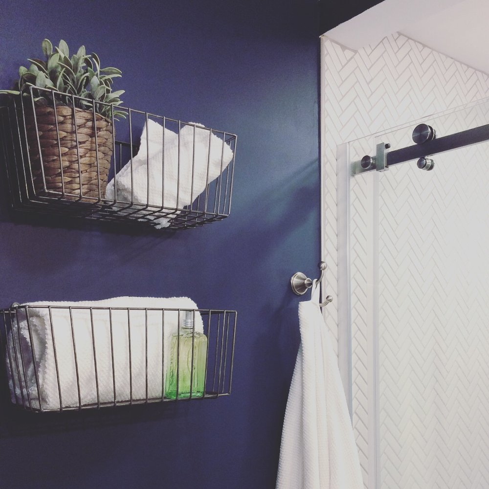 "Dark Blue and white master bath, ""Gentlemans Gray"" paint color by Benjamin Moore, white porcelain herringbone tile, brushed nickel finishes, wire baskets from Cost Plus World Market, from IKEA. Design by Beam&Bloom."