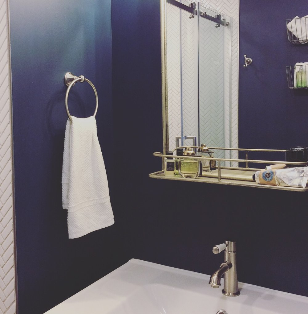 "Dark Blue and white master bath,""Gentlemans Gray"" paint color by Benjamin Moore, white porcelain herringbone tile, brushed nickel finishes, wire baskets from Cost Plus World Market, from IKEA. Design by Beam&Bloom."