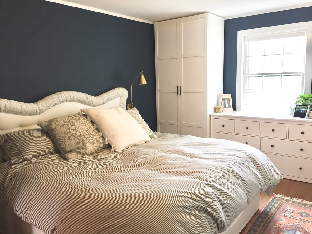 "Modern farmhouse bedroom, dark blue and white bedroom, ""Gentlemans Gray"" by Benjamin Moore. IKEA grey ticking bedding, storage ottoman, closet system and dresser. Plug in antique brass sconces from build.com. Ballard Designs bed skirt. Rejuvenation rug. Design by Beam&Bloom."