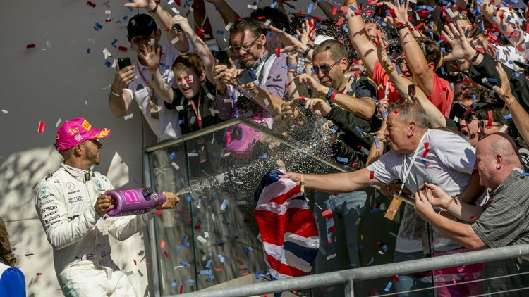 "Mercedes driver Lewis Hamilton celebrates his U.S. Grand Prix victory on Sunday while showering fans with champagne at Circuit of the Americas. He praised the annual event's atmosphere, saying, ""I think they just made the Super Bowl here."""