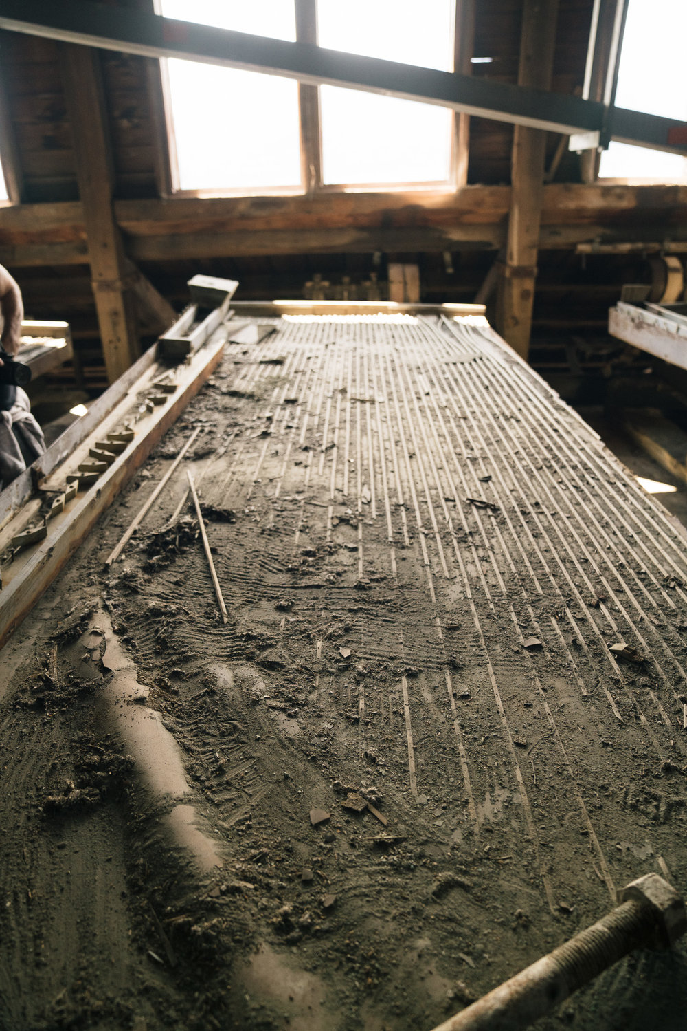 Rock was put in on one side of this table and then the table was shaken so the rocks jumped over the wooden lines, which increased in height over the width of the table. The lighter rocks would make it over every line and shake off, while the heavier, copper-filled rocks would stay on the table and sort themselves by density.