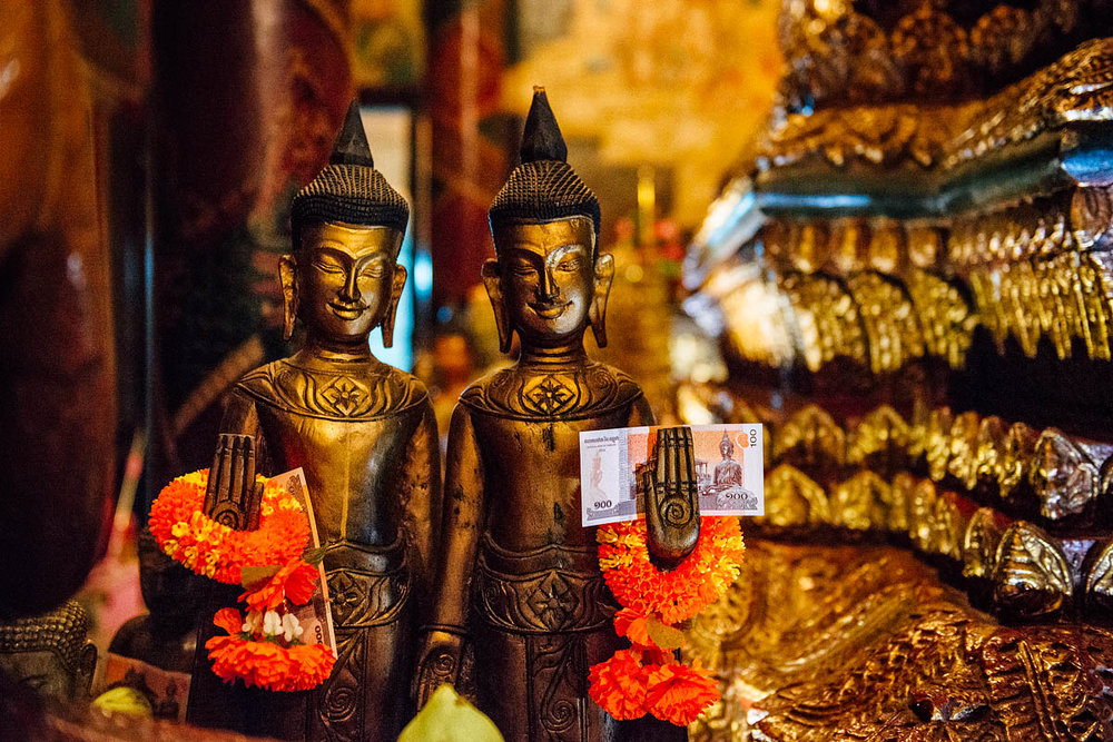 Buddha statues that hold money offered by the religious, inside the temlpe of Wat Phnom, Phnom Penh, Cambodia 2016