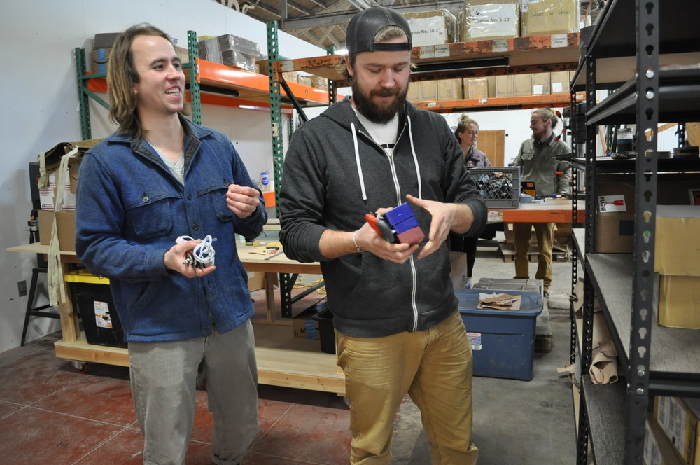 Adam (left) and Jason Gorske of DIY Bar organize storage shelves in their Annex workstation, while Hannah Teagle and Bar Smith of Maslow CNC chat in theirs.