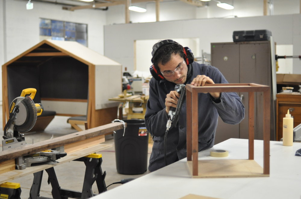 Nathan Dinihanian works on a teak side table in his Annex workstation.