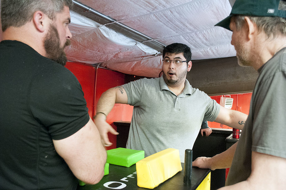 Isaac Saeidi (center) talks strategy with Will Dinwiddie (left) and Mike Barrett at an Epic Fitness Solutions practice.