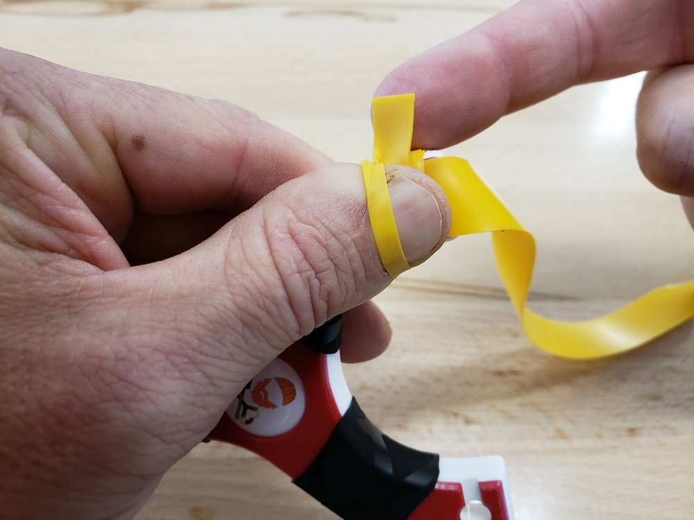 Step five: On the next wrap around, go underneath of your thumb and slowly pull the tie-on tail through the loop formed over your thumb