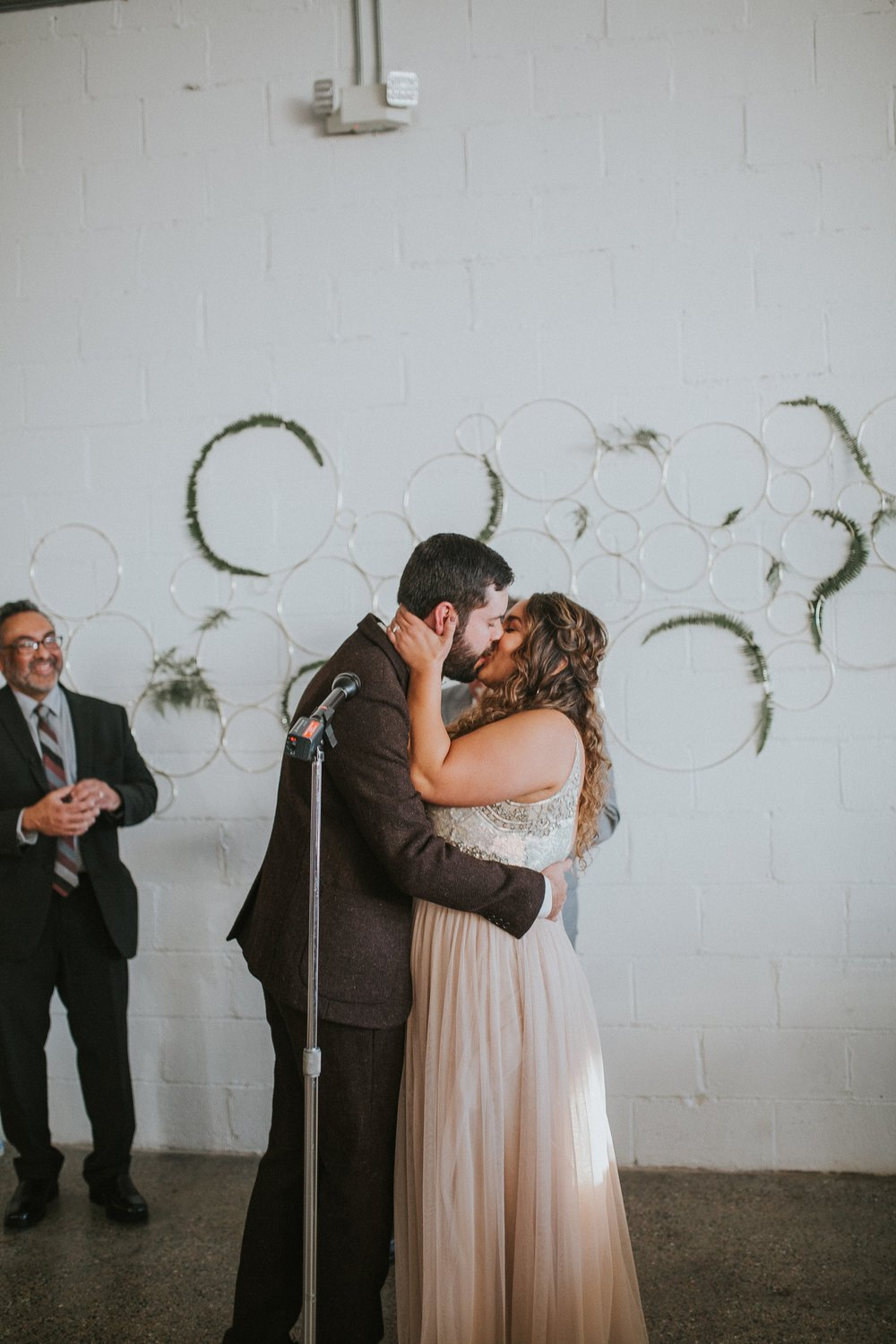 Smooches! These golden rings with greenery set the scene for Hank & Jessica's heartfelt ceremony.