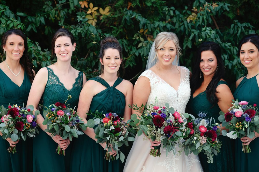Caitlin's floral palette really popped against her bridesmaids' emerald dresses.