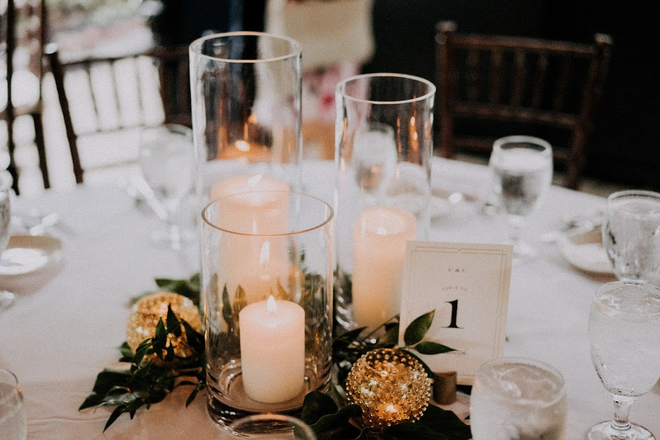 All of the candle centerpieces featured different hurricane glasses with gilded gold votive candle holders.