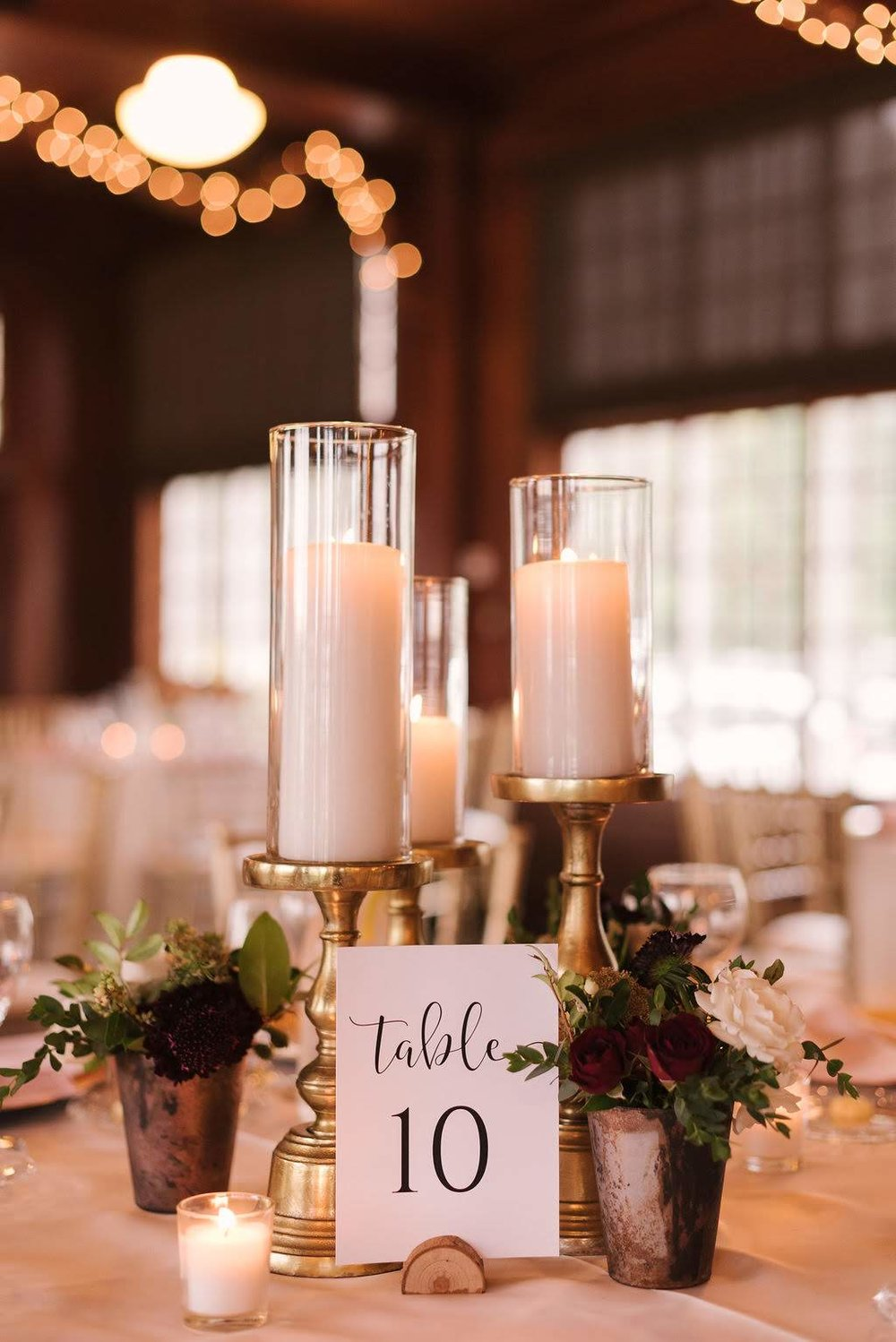 Pillar candles, votive candles and bud vases scattered around the room added a warm candlelit glow.