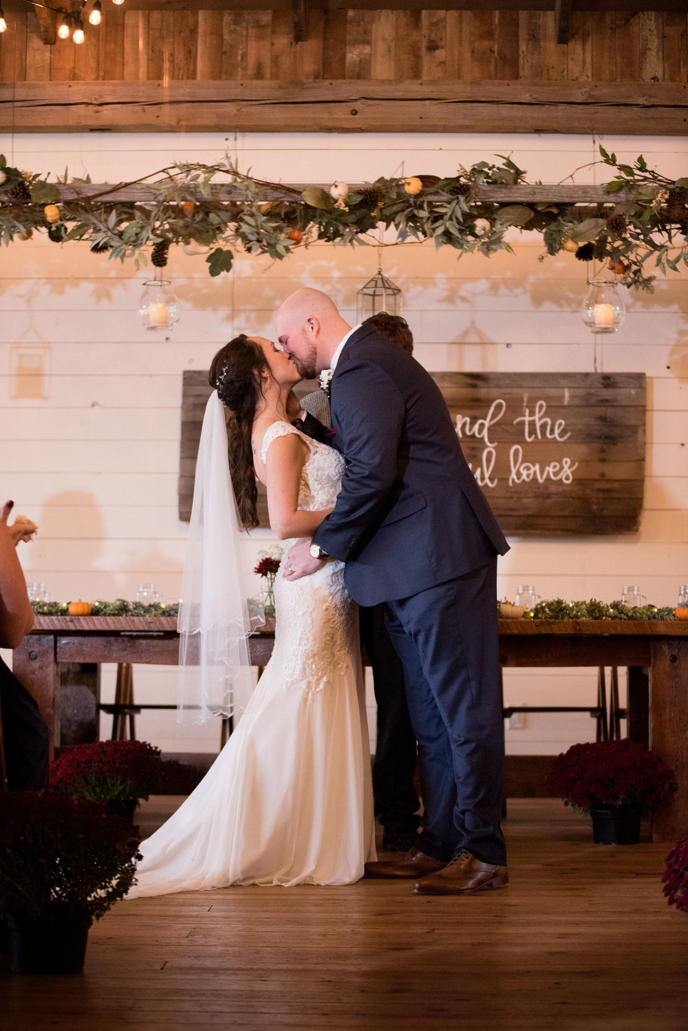 The ladder decor over the head table perfectly framed their ceremony and their sweet first kiss.