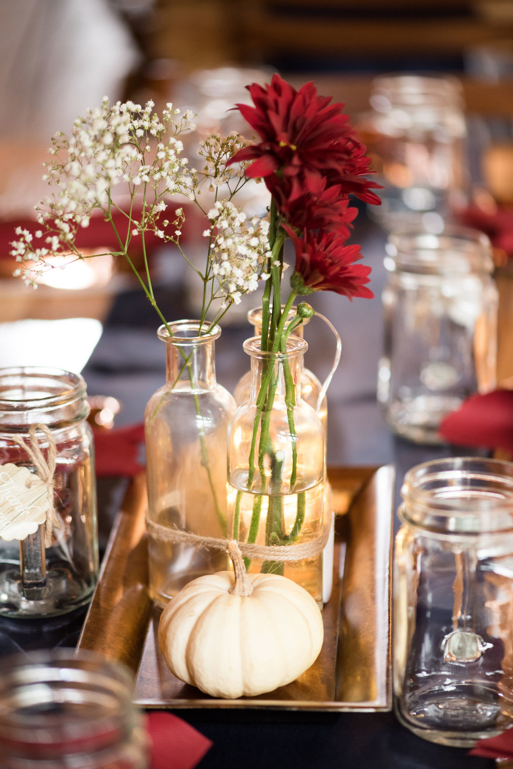 Katie and Dan fall centerpieces were mixed bud vases and gords with mason jar favors.