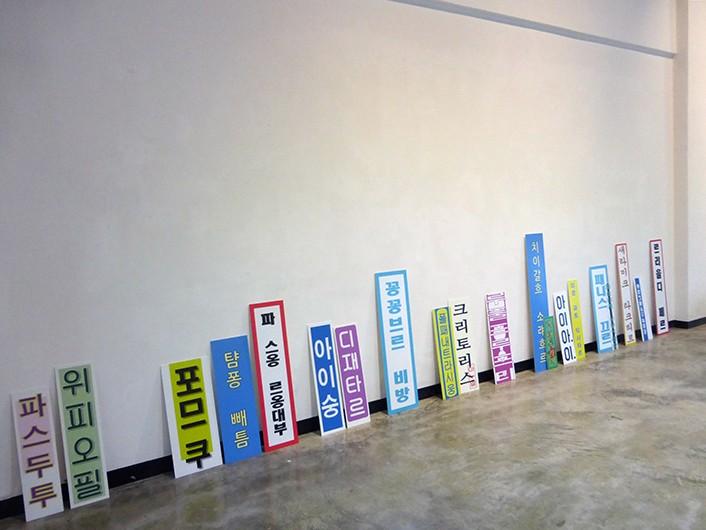 """Mistranslation #3 ou le village caché de samsumg , collaboration avec Eva Gerson, Textes en français à partir du texte  le village caché de samsumg (Eva Gerson) retranscrits phonétiquement en Coréen sur des pancartes en pvc, exposition """"Point it"""", Hongti Art Center, Busan, Corée du Sud, 2016"""