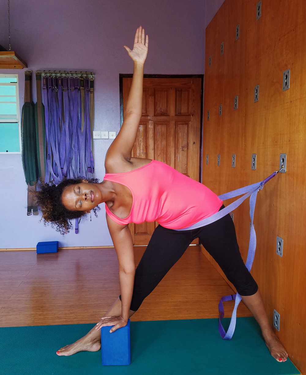 Carly Soul      writer, Reiki practitioner, therapeutic dance movement guide and soul worker, in Triangle Pose using the Spice Harmony Yoga wall system.