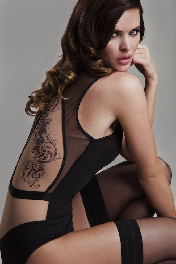 Image description: A model with light skin and long curled brown hair looks decisively over their shoulder into the camera. They are wearing a black mesh bodysuit with cutouts with black thigh-high stockings and appear to have a large back tattoo.