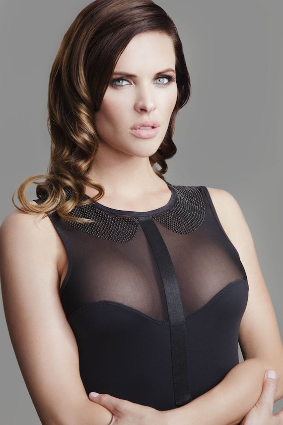 Image description: A model with light skin and long curled brown hair crosses their arms in front of them. They are wearing a black bodysuit with a mesh panel over the chest and a studded peter pan collar.