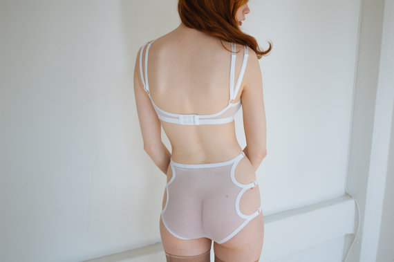 Image description: A model with light skin and long wavy red hair stands with their back to the camera. They are wearing a matching strappy white mesh bra and underwear set with beige thigh-high stockings.
