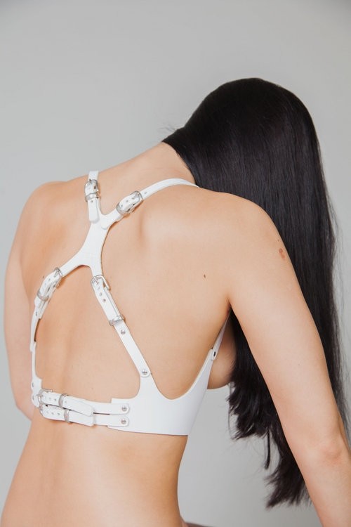 Image description: A model with light skin and long black hair sits with their back to the camera. They are wearing a white leather harness that forms an X shape across their back. Photo by Melissa Tofton Leather.