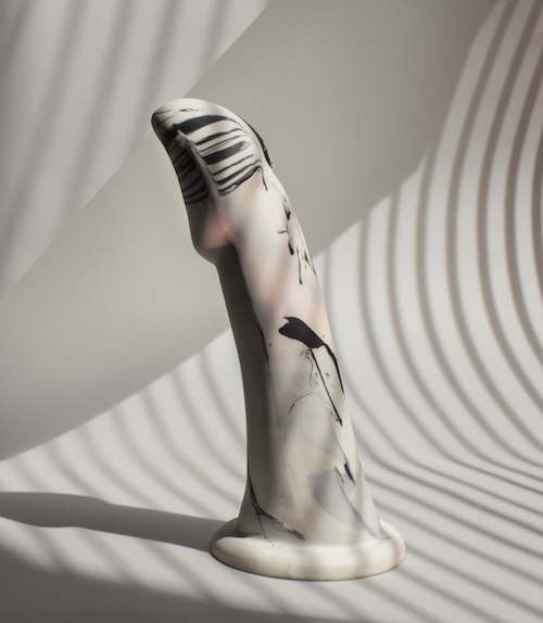 Image description: A white strap-on dildo with black splotches resembling ink stands on a white background. Linear shadow patterns provide contrast. Photo by Xenses Shop.
