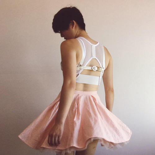 image description: A Chinese-American woman with short hair stands with her back to the camera. She is wearing a white leather bra over a white mesh crop top and pink circle skirt.