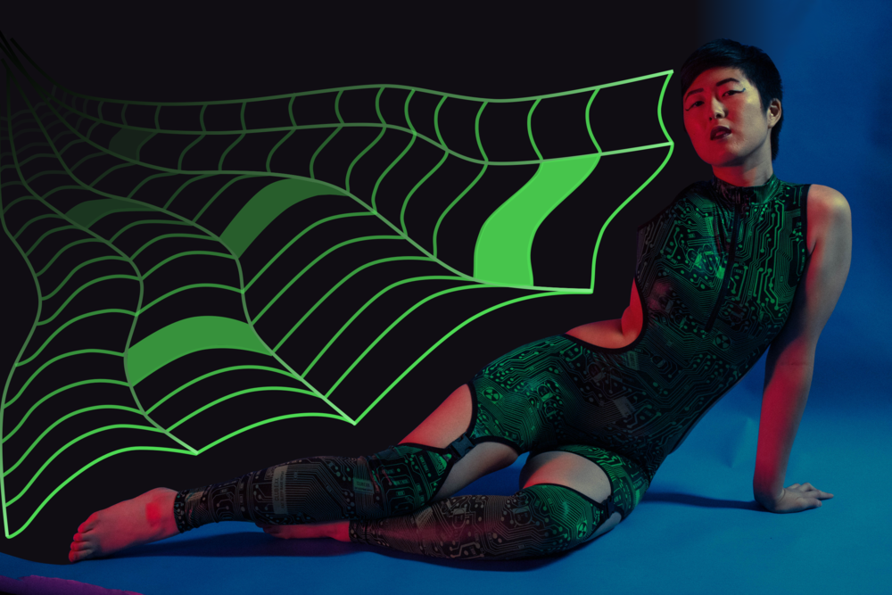 Me and my laser beams. Why do I need food if I only exist on the internet??   Photo by the incredibly talented  Nicole Aptekar , illustrations by me, bodysuit by  Dolls Kill  (out of stock, similar  here ).   Image description: A Chinese-American woman with short hair reclines on a blue background. She is wearing a neon green and black circuitry-patterned cutout bodysuit. Reaching out from the darkness behind her is a neon green illustrated web.