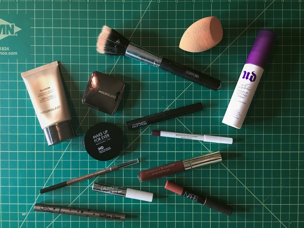 My familiar friends.   Image description: A variety of makeup items on a gridded green cutting mat.