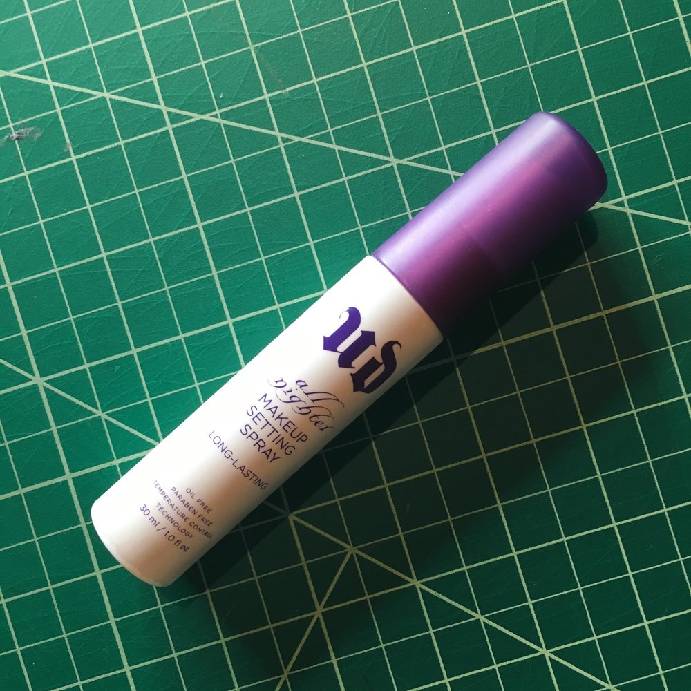 The final touch.   Image description: A white and purple tube of makeup setting spray on a gridded green background.