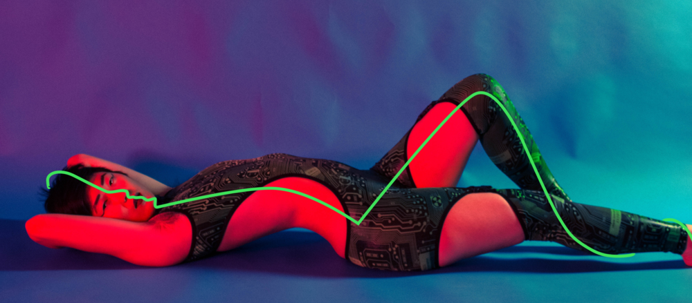 photo by Nicole Aptekar, edits by Estelle X   Image description: A Chinese-American woman with short hair reclines on a blue background. She is wearing a circuit-patterned bodysuit with cutouts and looking directly at the camera. An illustrated neon green line runs from the top of her head down the length of her body.